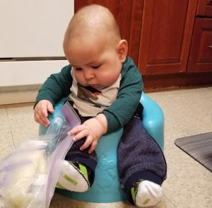 Baby Cinco playing with a milk bag for banco de leche