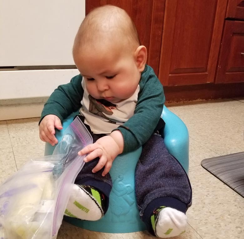 Bebé Cinco está jugando con una bolsa de leche para banco de leche