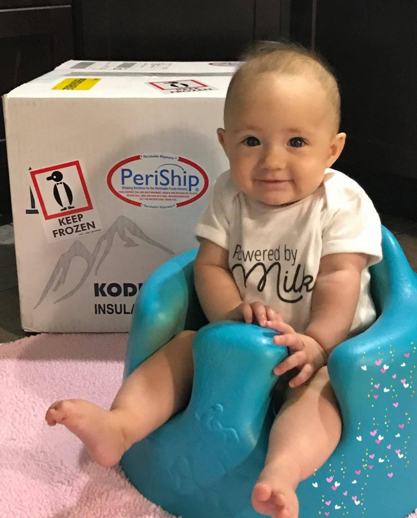 Baby with box of donated milk
