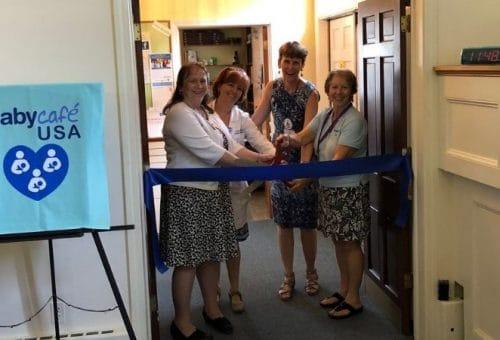 Community partners cutting ribbon at milk depot opening